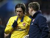Záložník Tomáš Rosický z Arsenalu opouští hřiště se zkrváceným nosem.