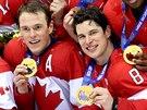 HOKEJOVÍ ŠAMPIÓNI. Kanadští hokejisté Ryan Getzlaf (zleva), Jonathan Toews a Sidney Crosby se zlatými olympijskými medailemi po vítězném utkání se Švédskem. (23. února 2014)