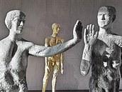 Z v�stavy Olbrama Zoubka na Hrad�. V pop�ed� jsou Chodci, kte�� se zdrav�, v pozad� vynik� zlat� socha Jana Palacha