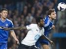 Branislav Ivanovic z Chelsea (vpravo) hlavičkuje balón do bezpečí před Emmanuelem Adebayorem z Tottenhamu.