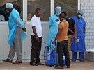 Zaměstnanci nemocnice v guinejské metropoli Conakry přijímají pacienta s podezřením na nákazu ebolou (29. března 2014).