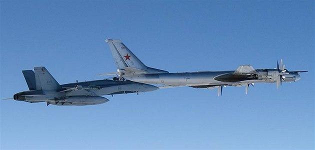 Ruský bombardér Tu-95 pod dozorem stíha�ky F/A-18 kanadských vzdu�ných sil.