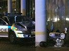 Honi�ka policejn�ho auta s motocyklem v Praze 11 skon�ila n�razem do sloupu u prodejny v��ivek (6. srpna 2014).