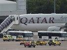 Cestuj�c� vystupuj� z letadla spole�nosti Qatar Airways, kter� na leti�t� v Manchesteru doprovodila st�ha�ka RAF (5. srpna 2014).