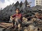 Palestinsk� chlapec sed� vedle zni�en� v�kov� budovy v Gaze (26. srpna 2014).