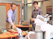 Lidsk� kolega se pro kameru zdrav� s robotick�m spolupracovn�kem a tak� ��fem. Robot mu toti� bude ��kat, co m� d�lat.