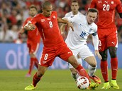 Kapitán anglické reprezentace Wayne Rooney atakuje švýcarského fotbalistu Goekhana Inlera.