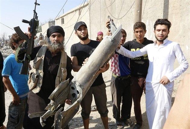 Bojovník Islámského státu ukazuje trosky syrského vládního letounu, které...
