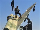 Bojovníci Islámského státu slaví dobytí letecké základny nedaleko syrského města Rakká (nedatovaný snímek)