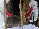 Zdravotníci vynášejí z domu na předměstí liberijské Monrovie muže s podezřením na ebolu a chystají se ho transportovat do izolace (31. října 2014).