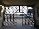 Hlavní brána koncentračního tábora v Dachau bez ukradené mříže s nápisem Arbeit macht frei.