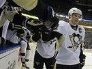 Sidney Crosby z Pittsbughu přijímá gratulace od spoluhráčů na střídačce.